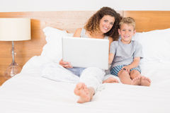 Happy mother and son sitting on bed using laptop Stock Photography