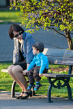 Happy mother and son sitting on bench in city park Royalty Free Stock Photo