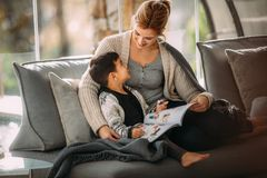 Mother and son with story book at home stock photography