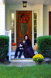 Happy mother and son sitting on the porch of the autumn decorated house Stock Photos