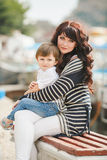 Happy mother and son sitting on the quay. Stock Photography