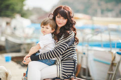 Happy mother and son sitting on the quay. Royalty Free Stock Photo
