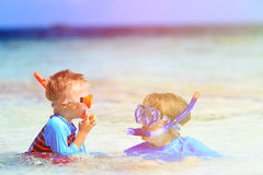 Happy mother and son snorkeling on beach Stock Photo