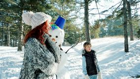 Happy mother and son spend together a winter vacation, family sculpts snowman, snow sculptures decorate stock video footage
