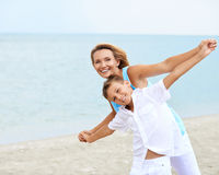 Happy mother and son standing on the beac. Royalty Free Stock Images