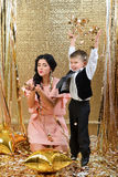 Happy mother and son throwing gold serpentine. New year's eve. Gold birthday party Stock Image