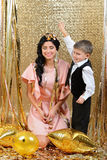 Happy mother and son throwing gold serpentine. New year's eve. Gold birthday party Royalty Free Stock Images