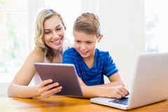 Happy mother and son using laptop and digital tablet. At home Stock Photos