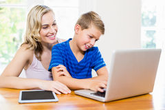 Happy mother and son using laptop. At home Stock Photo