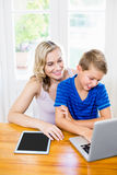 Happy mother and son using laptop. At home Royalty Free Stock Images
