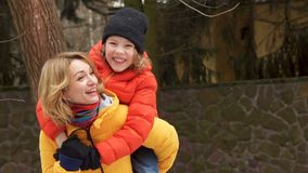 Happy mother and son on a walk. The boy is sitting on Mom`s shoulders, they laugh and laugh happily stock video