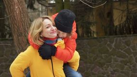 Happy mother and son on a walk. The boy is sitting on mom`s shoulders, they laugh and laugh happily stock footage