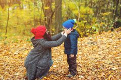 Happy mother and son walking and playing fun together in autumn park. Happy mother and son walking and playing fun together in the autumn park Royalty Free Stock Image
