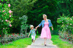 Happy Mother and son walking. In summer park with flowers Stock Photography