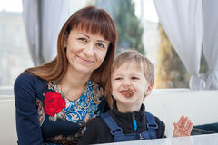 Happy mother and son. In a white style cafe royalty free stock photography