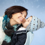 Happy Mother and Son in Winter Clothes. Happy family in winter clothing. Little son kissing his happy smiling mother on a cheek over blue Royalty Free Stock Image