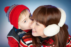 Happy Mother and Son in Winter Clothes. Happy family in winter clothing. Little son kissing his happy smiling mother on a cheek over blue Stock Image