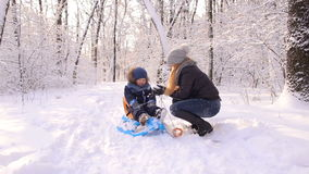 Happy mother and son in winter park having fun. stock footage