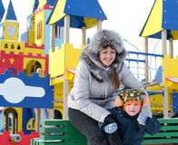 Happy mother and son in a winter playground Stock Images