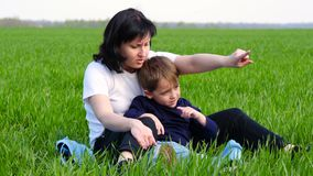 A happy mother spends time with her son, relaxing, sitting on the grass. A woman and a child point their fingers into