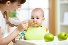Happy mother spoon feeding her baby child Stock Photo