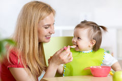 Happy mother spoon feeding her baby child Stock Photos