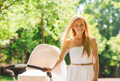 Happy mother with stroller in park Royalty Free Stock Image