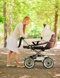 Happy mother with stroller in park Royalty Free Stock Photos