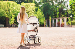 Happy mother with stroller in park Royalty Free Stock Photo