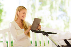 Happy mother with tablet pc and stroller in park Stock Photo