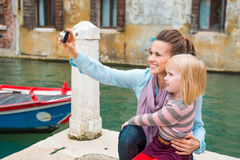 Happy mother taking photo in Venice while daughter is watching Stock Images