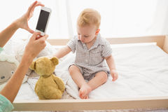 Happy mother taking a picture of her baby boy. At home in bedroom Stock Photo