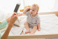 Happy mother taking a picture of her baby boy Royalty Free Stock Images