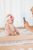 Happy mother taking a picture of her baby girl Royalty Free Stock Photo