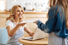 Happy mother taking a printout from her daughters hands. Pleased with work. Pleasant pretty women sitting at the table and taking a printout with calculations royalty free stock photo