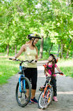 Happy mother talking with her daughter riding a mountain bike Royalty Free Stock Photo