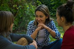 Happy mother talking to her children in the park. royalty free stock photo