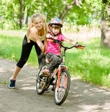 Happy mother teaches his daughter to ride a bike Royalty Free Stock Photography
