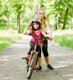 Happy mother teaches his daughter to ride a bike Royalty Free Stock Photo
