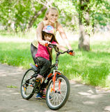 Happy mother teaches his daughter to ride a bike Royalty Free Stock Images