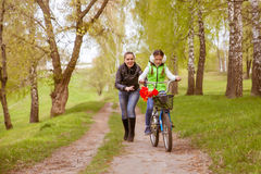 Happy mother teaches his daughter to ride a bike. A mother is glad to successes of daughter Royalty Free Stock Image