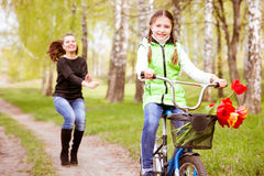 Happy mother teaches his daughter to ride a bike. A mother is glad to successes of daughter Stock Photo