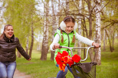 Happy mother teaches his daughter to ride a bike. A mother is glad to successes of daughter Royalty Free Stock Images