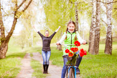 Happy mother teaches his daughter to ride a bike. A mother is glad to successes of daughter Stock Images
