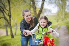 Happy mother teaches his daughter to ride a bike. A mother is glad to successes of daughter Stock Photos