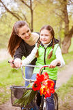 Happy mother teaches his daughter to ride a bike. A mother is glad to successes of daughter Royalty Free Stock Photography