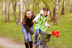 Happy mother teaches his daughter to ride a bike in the park. Parents teach their children . stock photo