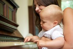 Happy mother teaching cute baby to play piano Stock Photo