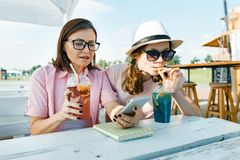 Happy mother and teen daughter talking and smiling. Parents with a kid in a summer outdoor cafe enjoying cold drinks on a hot. Summer day royalty free stock images