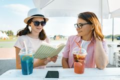 Happy mother and teen daughter talking and smiling. Parents with a kid in a summer outdoor cafe enjoying cold drinks on a hot. Summer day stock images